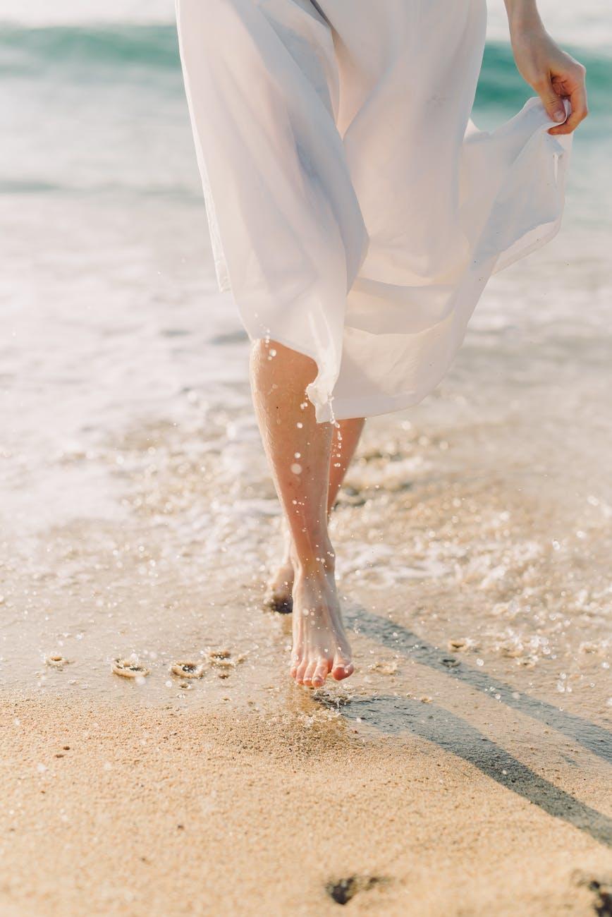 female barefoot walking on beach