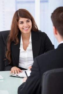 Happy young businesswoman interviewing male candidate at desk in office