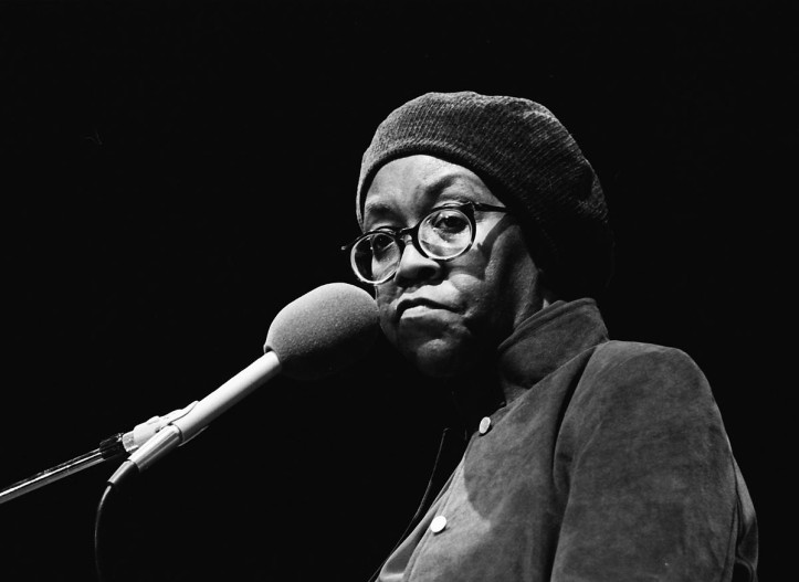 Portrait of Gwendolyn Brooks, wearing a hat, in front of a microphone with a black background.