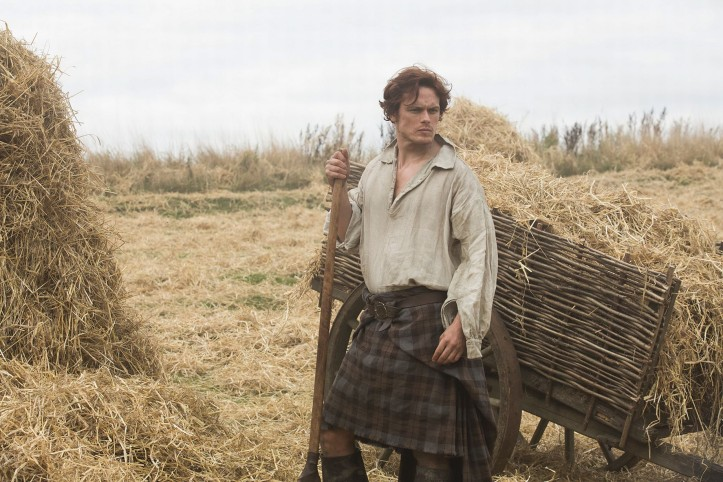 Outlander still frame of Jamie in a kilt next to a hay wagon looking very serious