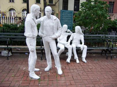Statues of four figures (two seated, two standing), painted white.
