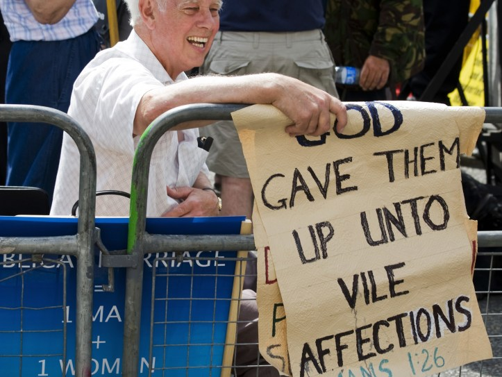 "Man holding sign that reads: ""God gave them up until vile affections"""