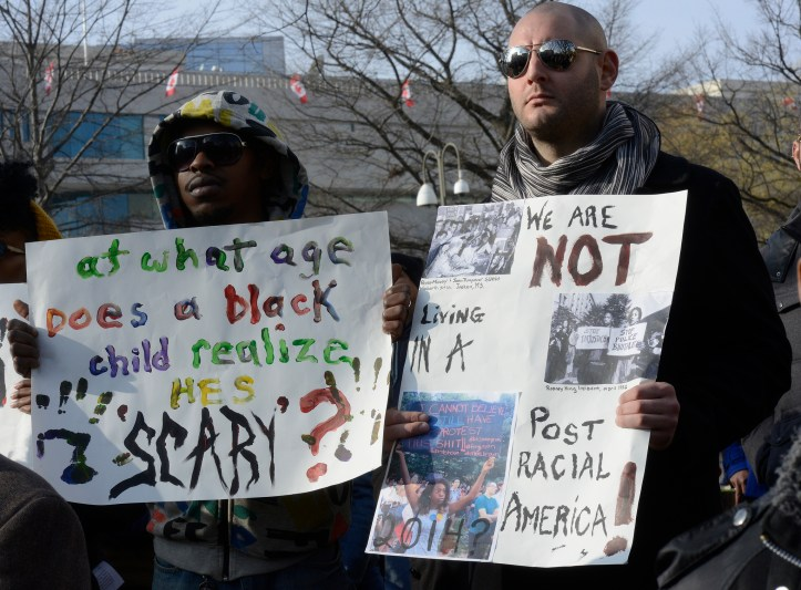 "Two protesters at Washington DC Justice for All Rally. Poster reading ""at what age does a black child realize he's scary?"""