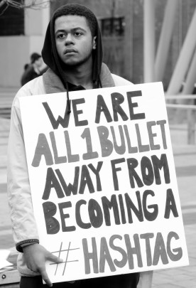 "Young man with a protest sign reading ""We are all 1 bullet away from becoming a #hashtag"""