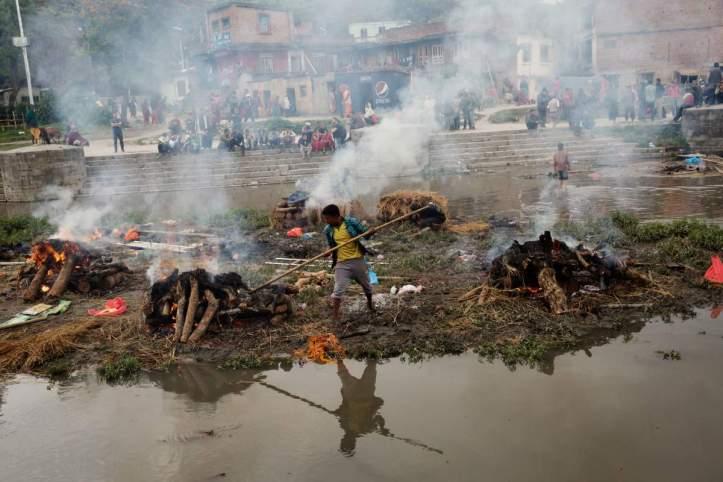 A Hindu man tending funeral pyres in Kathmandu, April 27, 2015. (Adam Ferguson/Time | All rights reserved)