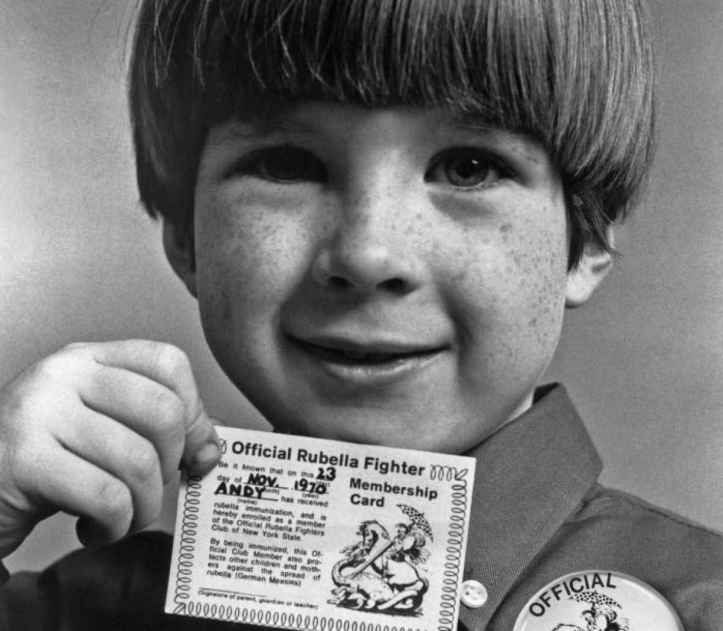 """A boy with his """"Official Rubella Fighter Membership Card"""", and button after being immunized for rubella during the """"rubella umbrella"""" campaign of the late 1960s, early 1970s, Public Health Image Library, CDC."""