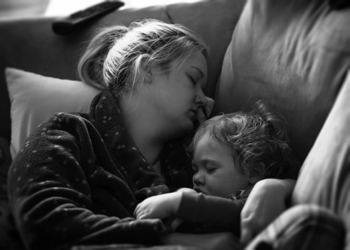 black and white photograph of a white woman holding a child in her arms, possibly asleep, and laying on a couch.