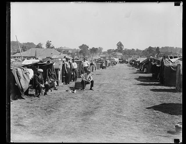 Black and white photograph of a dirt road lined with tents and men in various states of repose.