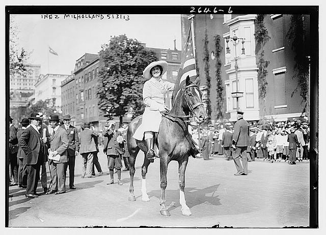 White woman in a long white dress and big white floppy hat rides a horse through the streets of Washington DC, followed by a crowd of men and women.