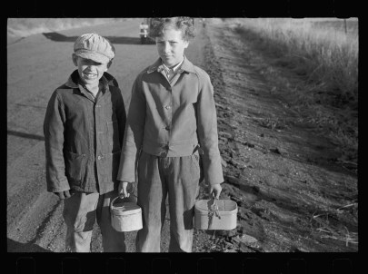 Black and white photo of two children in coats and pants, one child wearing a cap, and each carries a metal lunch pail.
