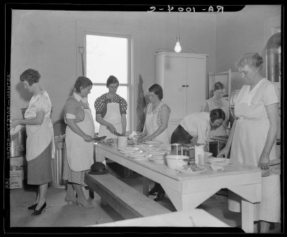 Seven white woman stand around a kitchen table, with bowls and ingredients laid out.