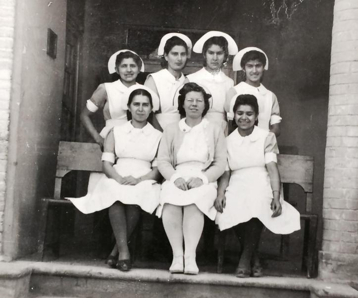 Black-and-white group portrait of seven women and girls in doctors uniforms