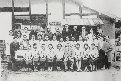 Black and white photo of a large group of people lined up in front of a building for a formal portrait