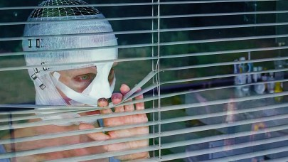 Woman with her face bandaged in gauze peers through venetian blinds.
