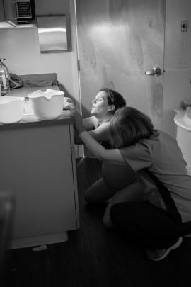 Grayscale photo of two women in a bathroom, crouched with their hands on the edge of a sink counter