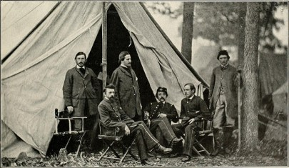 three men in Union uniforms sit in camp chairs, while three more men stand around then, also in Union uniforms. There is a large canvas tent behind them.