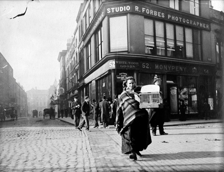 Black and white photo around the early 1900s, carrying a birdcage.