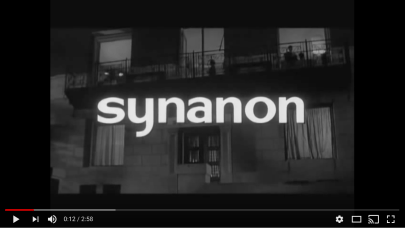 """The front of a building, with """"Syanon"""" written superimposed over it."""