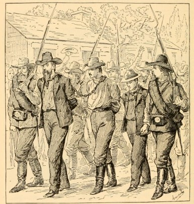 Two men in cowboy hats are marched with their hands tied behind their backs and surrounded by other men with guns.