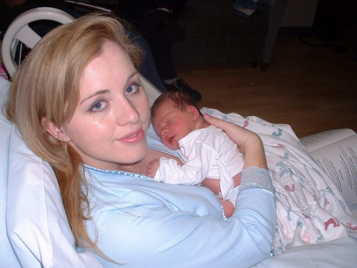 A white woman in a hospital bed holds a newborn baby.