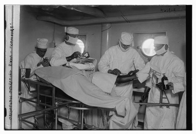 Three men in lab coats and masks surround an operating table. One holds a scalpel.