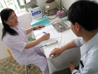 A Vietnamese woman in scrubs takes notes in an interview with a Vietnamese man.