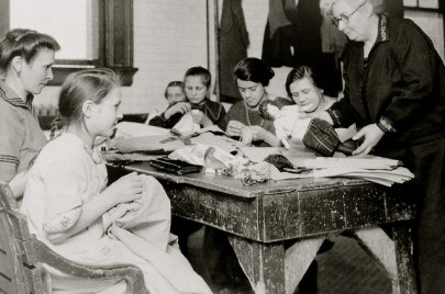 Black and white photo of children sitting at a wooden table, an old woman putting a doll on a blanket.