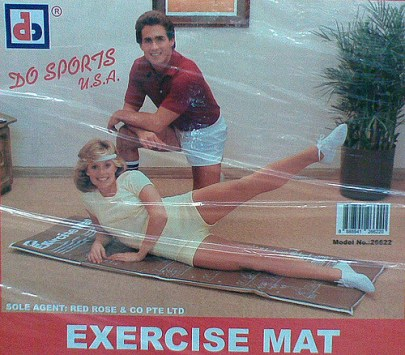 Photo on an exercise mat box. A white woman lays extended on mat doing a scissor kick, while a white man kneels beside her, presumable a trainer.