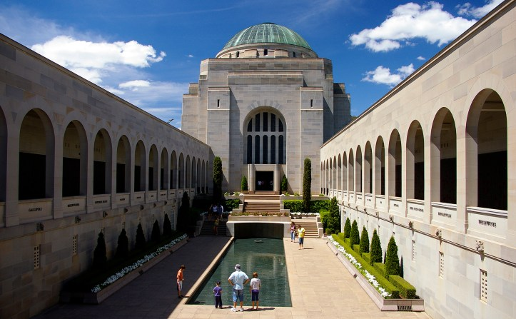 Photograph of the Australia War Museum from the front. A reflecting pool is surrounded by a large white stone edifice.