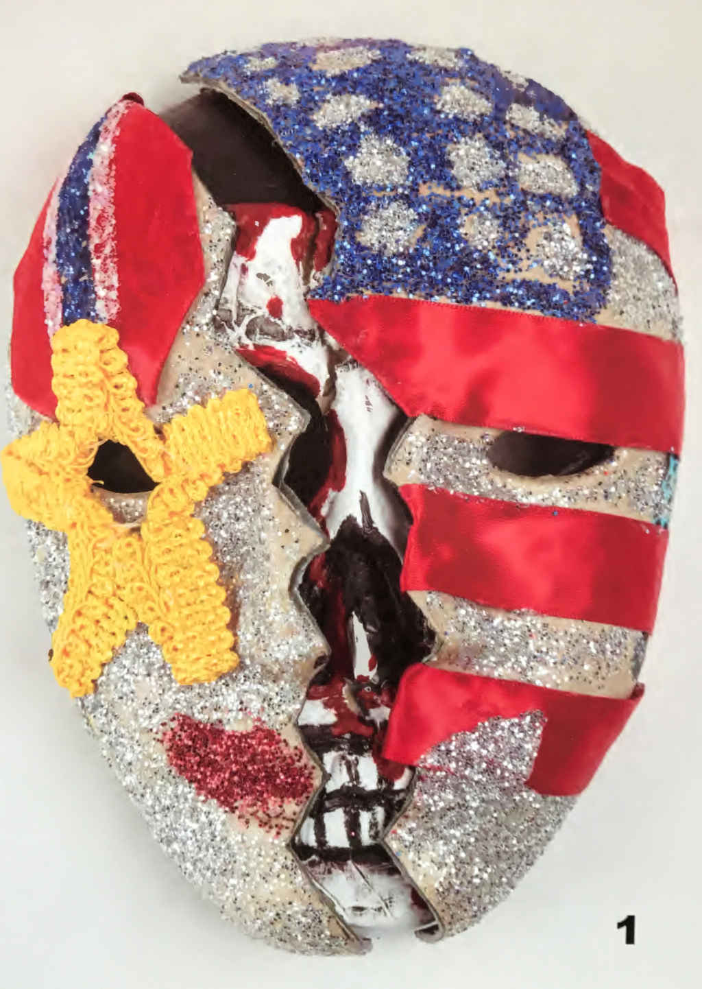 Photo of a face mask depicting a bloody skeleton peeking through a clean face draped in a glittering American flag