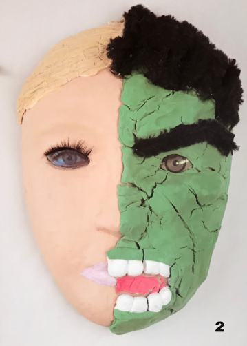 Photo of a face mask depicting one side of the face showing the normative conception of femininity that much of society still expects of her, while the other side shows anger and the effects of war, expressed in what looks like The Hulk