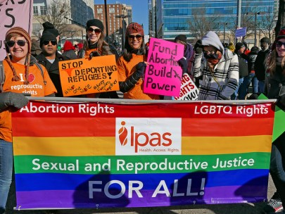 Photo of people marching with signs and a big rainbow flag banner. Signs demand abortion rights, LGBTQ rights, protection of immigrants.