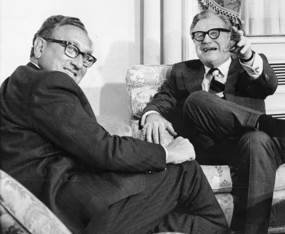 Two older white men in thick black rimmed glasses sit in arm chairs. One points cheekily at the photographer. Their body language indicates that they were deep in conversation