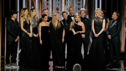 A group of actors in black evening wear stand on the stage at the Golden Globes. Reese Witherspoon is making an acceptance speech.
