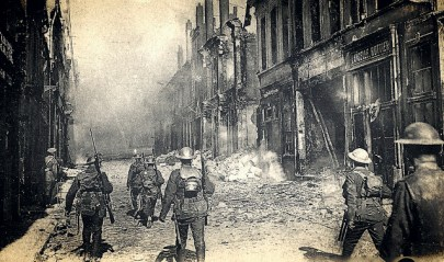 Three soldiers walk away from the camera; a building to the right has stone and other debris gathered at its base, and littering the street, from some kind of gun fight.