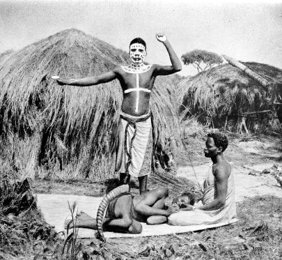 A man painted with his face painted white and a shoulders and chest also painted stands over someone who is curled in a fetal position on the ground beneath him. The painted man has his arms raised. There is a thatched-roof hut behind him.