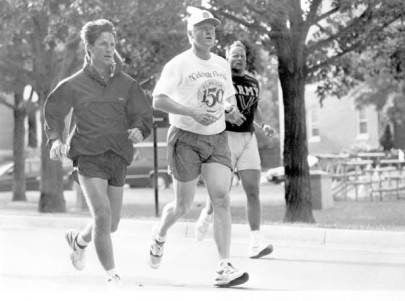 Black and white photo of President Bill Clinton jogging with two other people while wearing a Florida Sesquicentennial T-shirt.