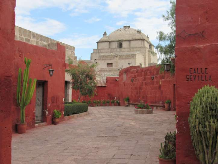 Photo of a red adobe walled courtyard with potted cacti and a tall domed tan building beyond the walls.