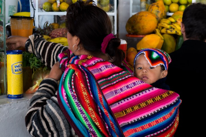 Photo of a woman carrying an infant on her back in a colorful blanket/satchel.