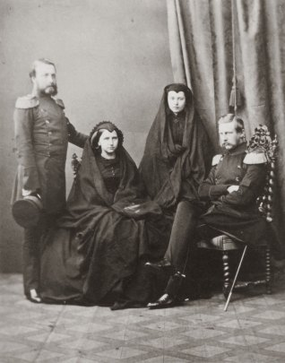 Two women and two men sit for a photograph. The women are dressed in heavy black gowns with veils.