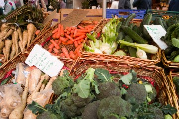 Photo of vegetables in baskets on a table, with labels declaring prices.