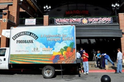 """Photo of a delivery truck with """"Food Bank"""" and other graphics on the side. Some people move a pallet of food stuffs nearby."""
