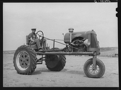 Black and white photograph of a man sitting on a tractor.