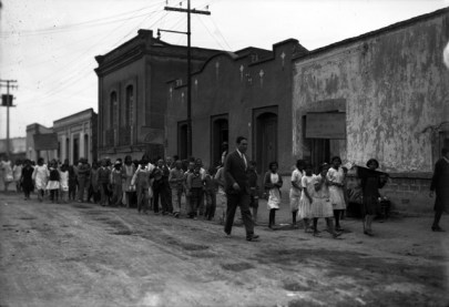 Black and white photo showing a large group of children parading down a street led by an adult.