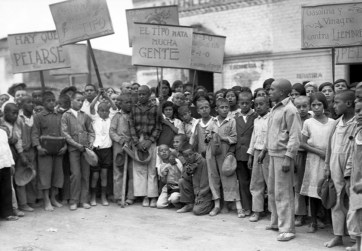 Photo of a large group of young children, most with shaved heads, holding signs with anti-typhus messages in Spanish.