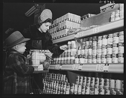 Black and white photograph of a white woman and a small boy standing in front of shelves stacked with canned goods.