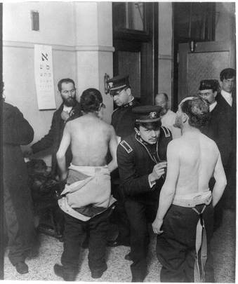 Photograph shows immigrants gathered in small room, two with shirts off being examined by physicians; eye chart written in Hebrew hangs on wall.