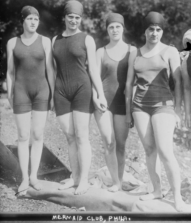 Four women standing on a beach wearing swim caps and swimsuits with a scooped neckline that end in shorts above the knee.