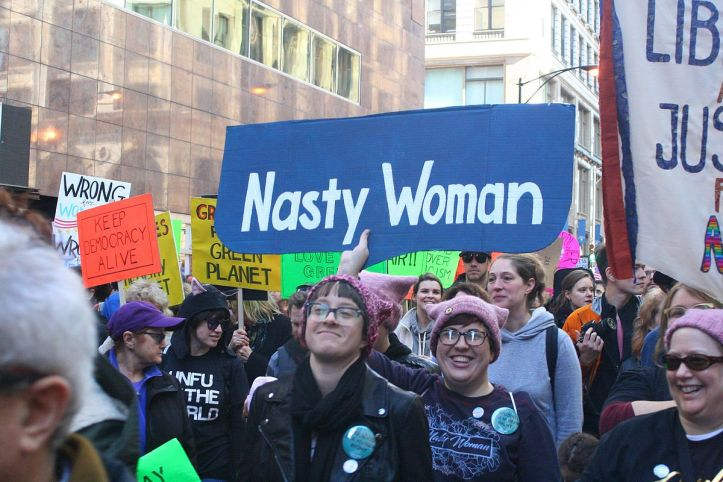 "Large group of people marching in a protest holding signs, the largest reads: ""Nasty woman."""