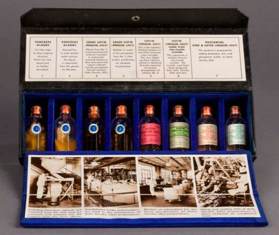 An open box containing eight small glass vials containing ingredients in the steps of the insulin manufacturing process around 1940.